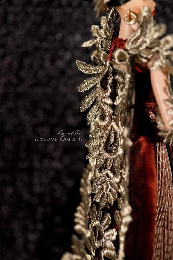 """Chiếc áo dài của đại diện Việt Nam tại Hoa hậu Búp bê Thế giới 2016 có tên gọi """"Khổng tước vọng nguyệt"""", lấy ý tưởng từ vẻ đẹp của chim công soi mình dưới ánh trăng vàng. Những đường nét trên áo đều được cân đo khá kĩ lưỡng để thực hiện trọn vẹn ý đồ của người thiết kế."""