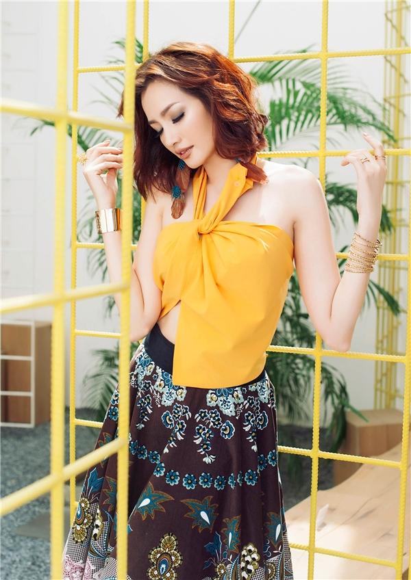 Váy, áo cách tân từ chiếc cổ yếm truyền thống được ứng dụng khá nhiều trong một vài năm trở lại đây. Chúng mang đến vẻ ngoài gợi cảm nhưng vẫn chừng mực cho người mặc. Trúc Diễm khéo léo tạo nên sự cân bằng giữa sáng - tối qua chiếc áo màu vàng cam rực rỡ cùng chân váy họa tiết với nền nâu đất trầm mặc. Phần áo tạo điểm nhấn bởi những đường cắt, khoét hiện đại theo kĩ thuật xoắn vải.