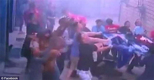 Đám đông đứng bên dưới giăng bạt để giúp 3 đứa trẻ và mẹ của chúng hạ cánh an toàn. Ảnh: Internet