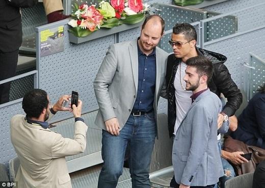 Ronaldo chụp ảnh cùng người hâm mộ, nhưng khó chịu trước cánh báo chí.Ảnh: BPI.