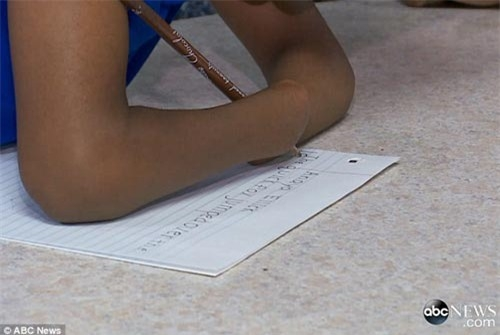 Cô bé gập khuỷu tay lại và kẹp bút chì vào giữa hai đầu tay.