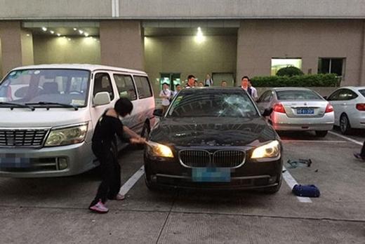 Không ngại trả thù giữa thanh thiên bạch nhật, một bà vợ ở Trung Quốc đã dùng búa phá tan chiếc xe của chồng, nơi ông ta và bồ nhí âu yếm nhau trước sự tình cờ chứng kiến của bà. (Ảnh: Internet)