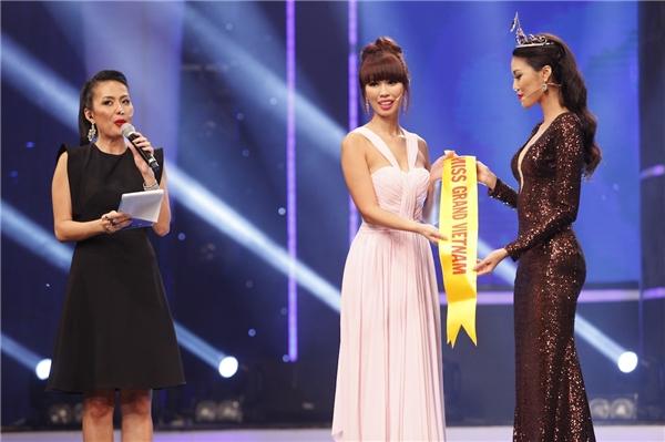 Hà Anh đón nhận băng đeo tượng trưng của Hoa hậu Hòa bình Thế giới từ tay Lan Khuê.