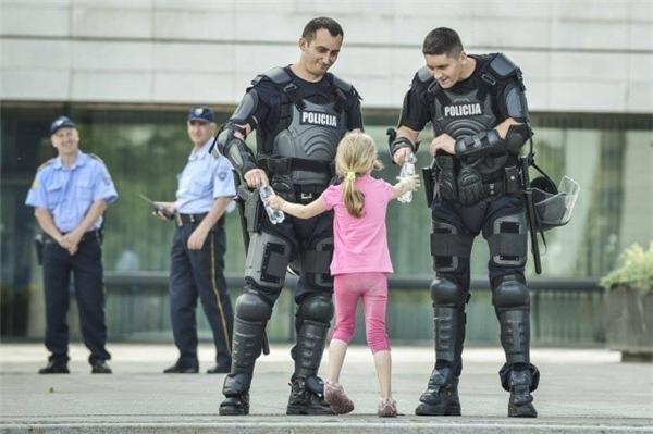 Cô bé mang nước uống cho hai nhân viên cảnh sát đang vất vả làm nhiệm vụ tại Liên bang Bosnia và Herzegovina.