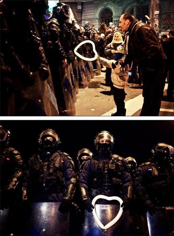 Một cậu bé Romania trao quả bóng hình trái tim cho cảnh sát chống bạo động trong cuộc biểu tình ở Bucharest.
