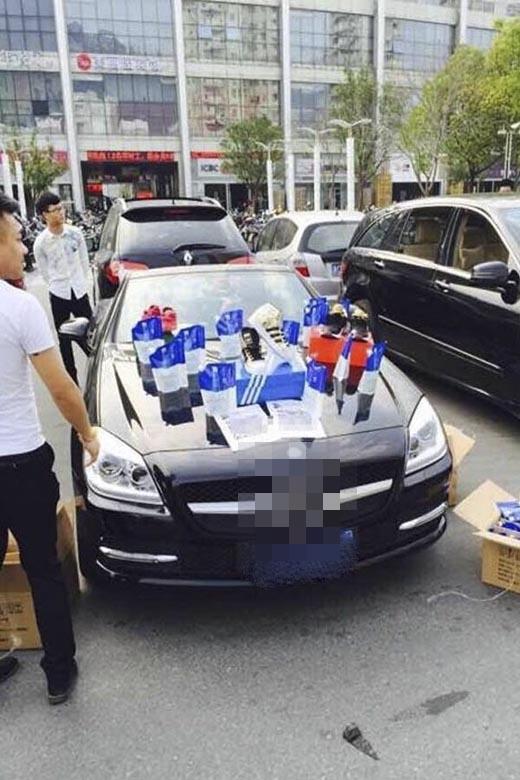 Các sản phẩm của các thương hiệu nổi tiếng được bày bán trên mui của những chiếc xe sang chảnh ngoài đường. (Ảnh: Internet)