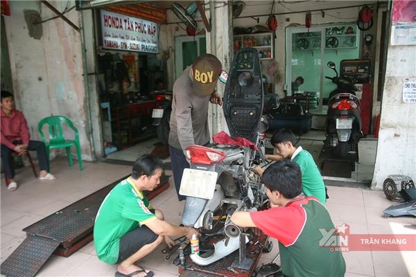 Bốn người thợ học việcđang sửa chữa xe cho khách hàng.