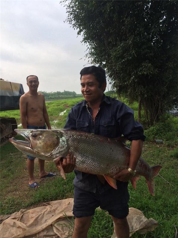 """Anh chàng tỏ ra vô cùng phấn khởi khi tự tay bắt được con cá """"to như người"""". (Ảnh: Internet)"""