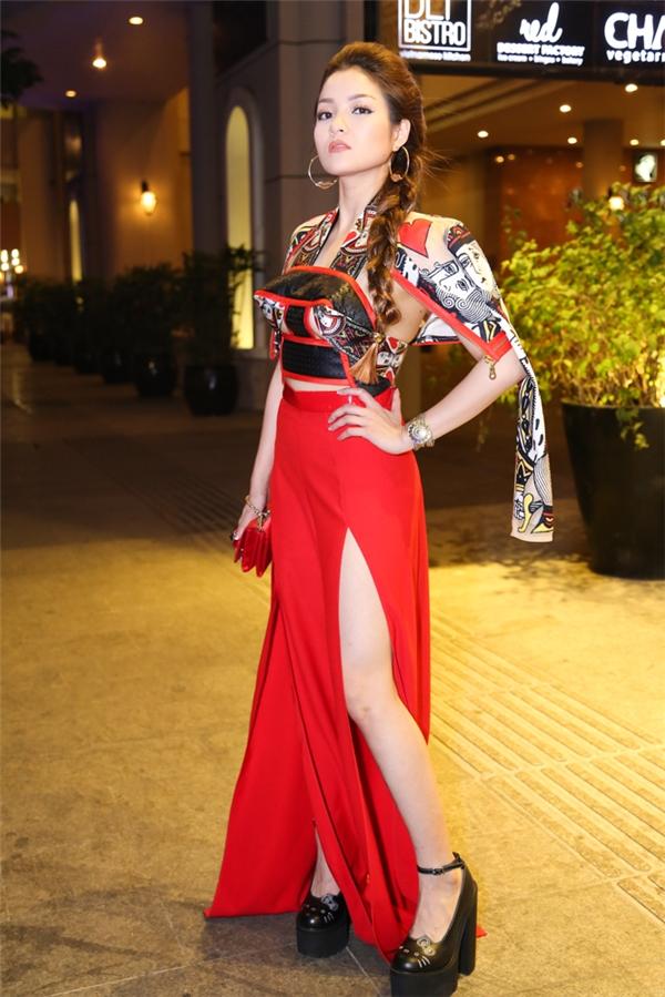 Thủy Top diện trang phục cầu kì với hai tông màu đỏ, đen truyền thống.