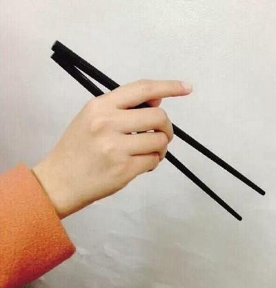 Cách cầm hờ hững, điệu đà: Ngón trỏ chếch lên trên, ngón cái và ngón giữa điều khiển đũa.
