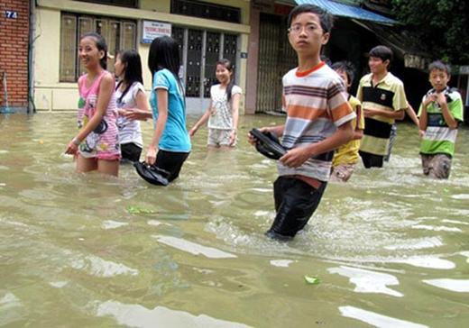 Dù mưa ngập là vậy nhưng cũng không cản được tinh thần học tập, ý chí cầu tiến của các em nhỏ. (Ảnh: Internet)