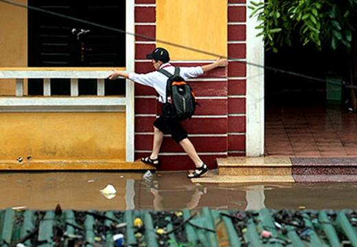 May mắn cho em học sinh này vì mưa vẫn chưa dâng lên lút các thềm nhà. (Ảnh: Internet)