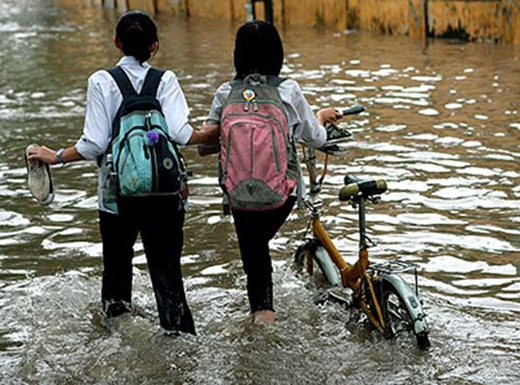 Dù ngập lụt thì đôi bạn vẫn bình thản dắt tay nhau đi. (Ảnh: Internet)