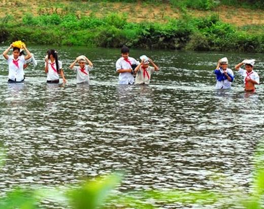 Lội qua con sông này các em chỉ biết giơ cao cập lên đầu để tránh ướt tập vở thôi. (Ảnh: Internet)
