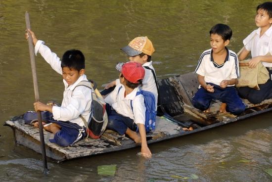 Có những nơi các em học sinh phải tự chèo bè để sang sông. (Ảnh: Internet)