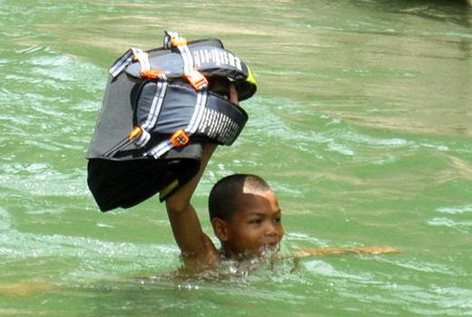 Nước ngập đến lút cằm, em nhỏ này chỉ còn biết bơi qua sông, ưu tiên chiếc cặp của mình không bị ướt. (Ảnh: Internet)