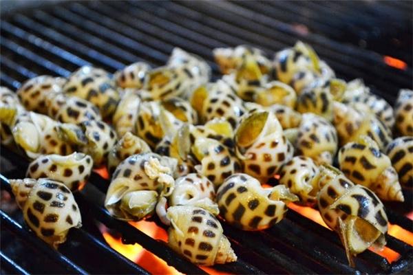 Ốc hương hấp dẫn nhất là khi nướng gần chín, thêmchút mỡ hành hoặc dầu ăn vào miệng ốc rồi tiếp tục nướng, thịt ốc sẽ trở nên vàng ruộm và bốc mùi thơm nức.(Ảnh: Internet)