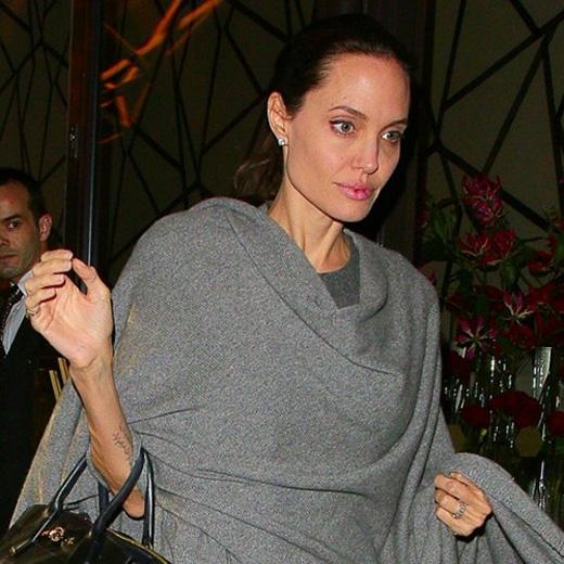 Một tháng sau tại London, Jolie giấu mình trong trang phục màu xám nhiều lớp.
