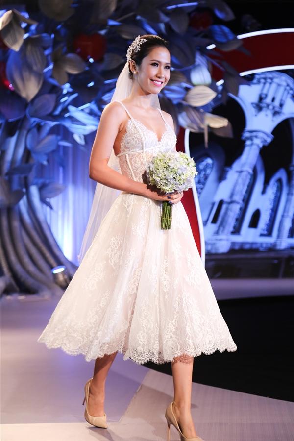 Nữ người mẫu trình diễn bộ váy xòe ngắn trên nền chất liệu ren theo cấu trúc đối xứng. Phần trên của váy trông vô cùng gợi cảm bởi thiết kế hai dây mỏng manh.