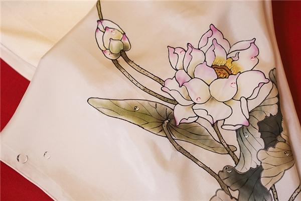 Mẫu thiết kế lấy sắc xám đen sang trọng làm chủ đạo. Đi kèm áo dài là chiếc quần lụa trắng ống suông thanh lịch. Phụ kiện là khăn lụa trắng với họa tiết hoa sen mềm mại, ngọt ngào.