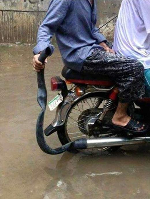 Nối dài ống xả xe máy bằng ống nhựa hoặc xăm lốp bỏ đi là cách nhiều người sử dụng để kiếm tiền từ người đi đường.