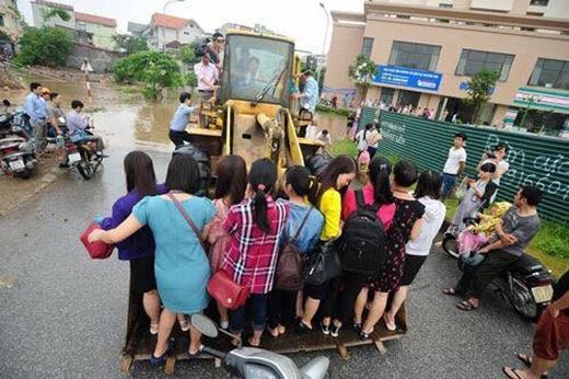 Xe cẩu chở người đi đường qua đoạn ngập lụt để kiếm tiền.