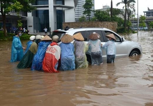 Một cách kiếm tiền khác cũng nở rộ mùa ngập lụt đó là dịch vụ đẩy xe máy qua chỗ ngập lụt với giá 20.000 - 50.000 đồng.