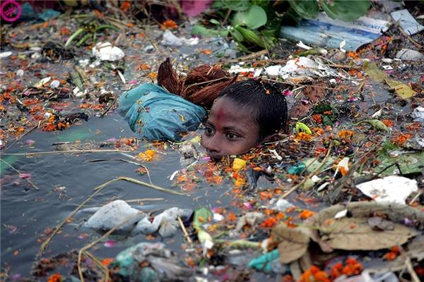 Một cậu bé khác thì phải bơi lội trong dòng sông rác ở quê hương Ấn Độ của mình.