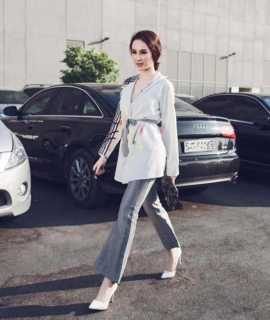 Phương Trinh thanh lịch với set đồ kết hợp áo xẻ ngực họa tiết cùng quần âu ống loe tông xám trắng cổ điển.