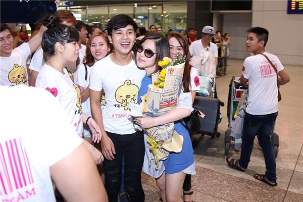 """Cặp đôi Bùi Anh Tuấn và Hương Tràm vừa xuất hiện ở cửa sân bay ngay lập tức bị fan """"vây kín"""" không lối thoát. Có thể thấy tình cảm mà FC """"Trại gà"""" dành cho Hương Tràm vô cùng lớn, bởi lúc đó đã là nửa đêm mà họ vẫn nán lại chờ đợi cô."""