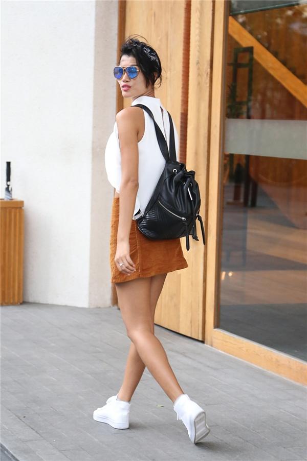 Người mẫu Trang Lạ kết hợp chân váy midi màu vàng nâu ấm áp cùng áo phông trắng đơn giản.