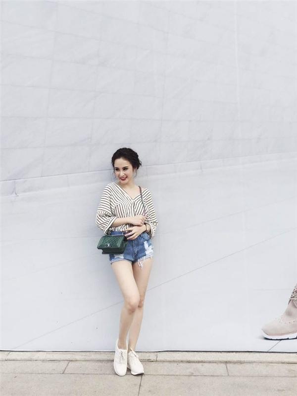 Angela Phương Trinh khoe chân dài trong chiếc quần short jeans denim hợp xu hướng. Nữ diễn viên chọn phối cùng áo sơ mi kẻ sọc hở vai gợi cảm, trẻ trung.