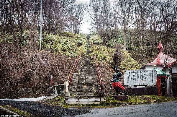 Ngay cả lối đi dẫn lên chùa cũng bị cỏ dạimọc um tùm chứng tỏ không có ai đi từ rất lâu. Bức tượng phía dưới thậm chí còn bị cụt một tay. (Ảnh: Prett Patman)