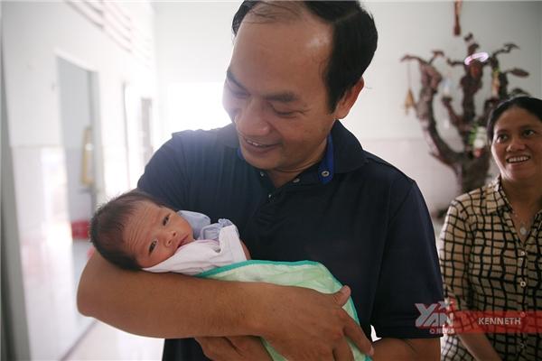 Linh mục Tịch bế một embé sơ sinh15 ngày tuổi trong không khí vui vẻ của mọi người tại trung tâm.