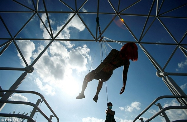 """Khoảnh khắc """"toả sáng"""":Kaitlin được treo ngửa trên một giàn kim loại. (Ảnh: Internet)"""