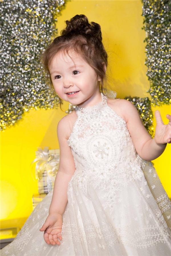 Phần váy dài tạo nên vẻ ngoài đáng yêu và độc đáo cho cô bé. Sự giống nhau không chỉ ở trang phục đôi, mà còn ở kiểu tóc và phụ kiện túi xách.