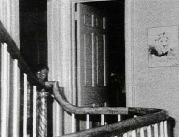 """Bức ảnh này được chụp tại ngôi nhà ma ám Amityville, New York, Mỹ trong một cuộc điều tra của các nhà nghiên cứu. Họ không biết ai đã chụp tấm ảnh này, và cam đoan trong đoàn không hề có trẻ em. Tấm ảnh chỉ tự nhiên xuất hiện trong số các bức ảnh khác họ chụp. Đứa trẻ """"ma"""" trong hình được cho là linh hồn xấu số của một cậu bé bị giết 3 năm về trước.(Ảnh: Internet)"""
