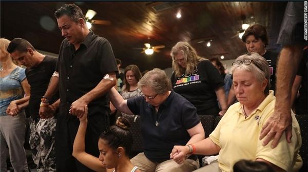 Người đàn ông mặc áo đen với cánh tay bị thương là một trong số những nạn nhân may mắn sống sót sau đêm kinh hoàng tại hộp đêm Pulse. Anh đang cầu nguyện cho các nạn nhân cùng những người khác tại nhà thờ Joy Metropolitan ở Orlando. (Ảnh: CNN)