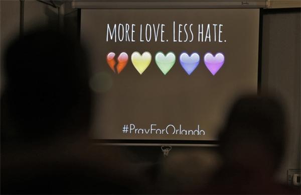 """""""Hãy yêu nhiều hơn, ghét ít lại"""" – thông điệp xuất hiện trong buổi tưởng niệm tại nhà thờ Joy Metropolitan. (Ảnh: AP)"""