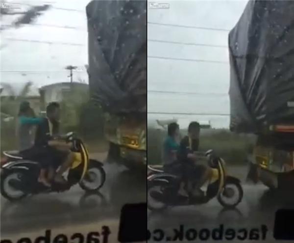 Điều khiển xe chạy cực gầnđuôi xe tải, hai thanh niên này bất chấp tính mạng của mình. (Ảnh cắt từ clip)
