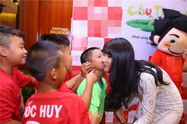 Diệp Lâm Anh trong vòng vây của những cầu thủ nhí. Cô vui vẻ để các em ôm hôn nồng nhiệt.
