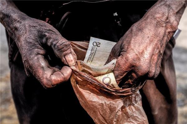 Công nhân bỏ tiền vào túi ni lông cẩn thận để bảo quản đồng lương ít ỏi của mìnhkhỏi ẫm ướt.