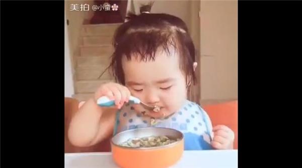 """Cô bé lập tức """"im thin thít"""", tập trung ăn uống,sau khi được đeo khăn ăn lên cổ.(Ảnh : Internet)"""