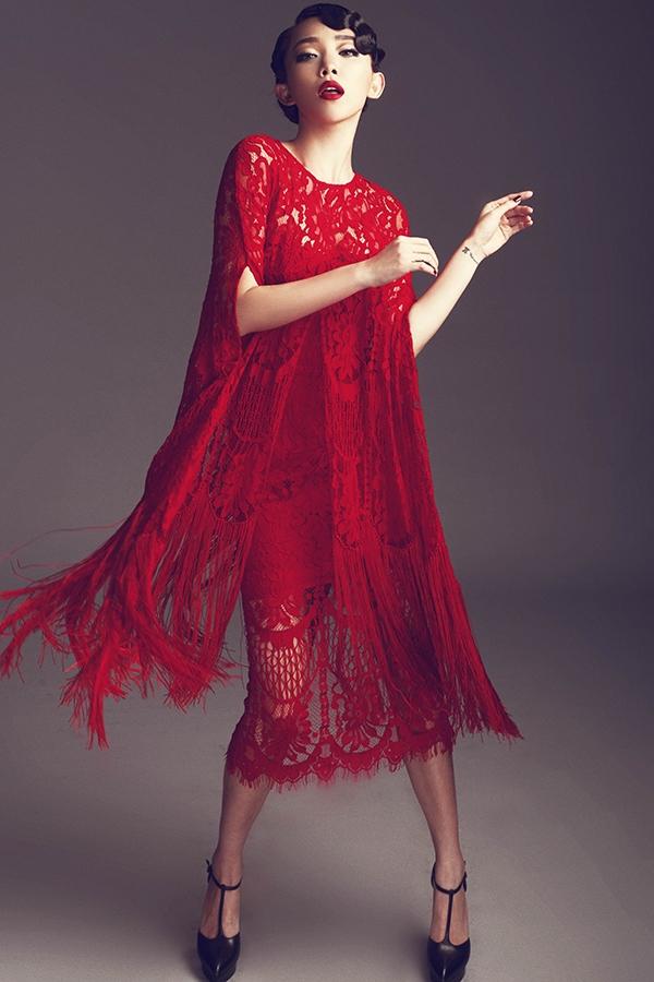 Cùng sử dụng sắc đỏ và chất liệu ren, lưới, thiết kế này lại là sự kết hợp hoàn hảo giữa váy ôm sát và áo choàng xẻ tay. Tua rua hòa quyện vào trong những họa tiết ren to bản.