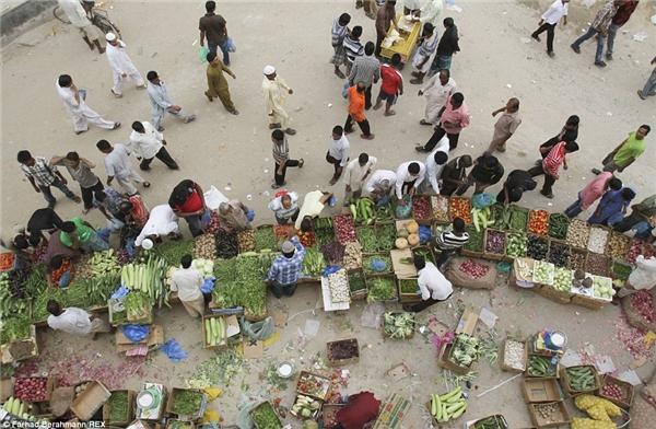 Chợ rau củ nằm khuất sâu trong khu ổ chuột Sonapur là nơi những người lao động nhập cư thường lui tới để mua rau quả với giá rất rẻ.(Ảnh:Farhad Berahman)