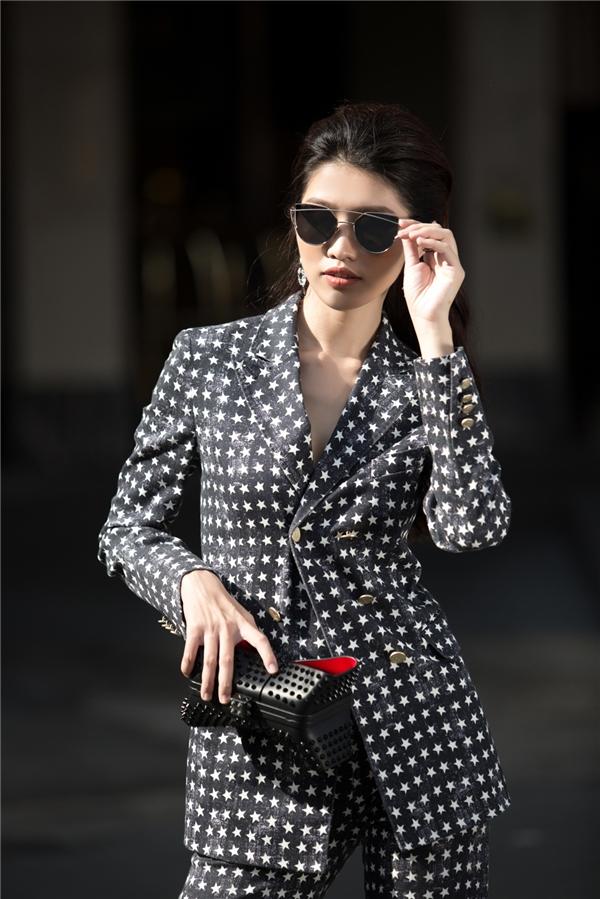 Đi kèm bộ trang phục là ví cầm tay nạm đinh tán với thiết kế lạ mắt, mắt kính mặt gương trẻ trung, ấn tượng.