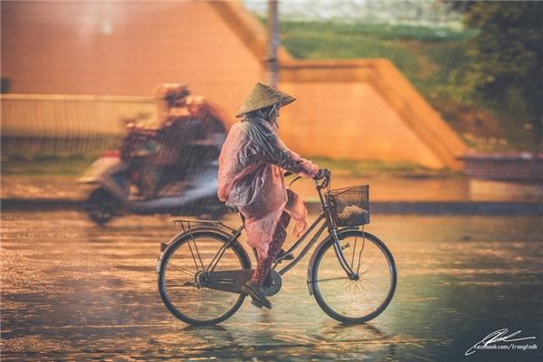 Để rồi cầu cho trời đừng mưa mãi, để những chiếc áo mưa mỏng dính, rẻ tiền kia còn lành lặn cho đến khi về đến nhà. (Ảnh: Lưu Khúc)