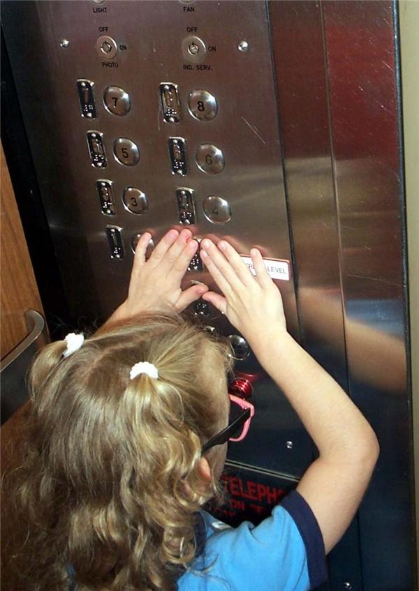 Một em bé khiếm thị đang đọc chữBraille trong thang máy.