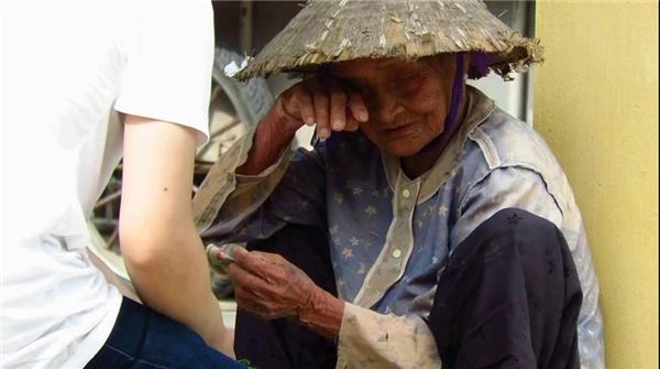 Nước mắt của cụ bà bán rau chỉ kiếm được 10 nghìn một ngày khi nhận được giúp đỡ. (Ảnh: Internet)