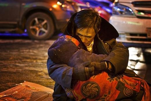Hình ảnh người đàn ông Trung Quốc hơn 60 tuổi đang ôm chặt xác người vợ. Được biết, ông đã ôm người vợ đã chết như thế suốt 2 tiếng đồng hồ dưới tiết trời lạnh thấu xương thấu thịt (khoảng -24 độ C) của thành phố Thẩm Dương, tỉnh Liêu Ninh, Trung Quốc. (Ảnh Internet)